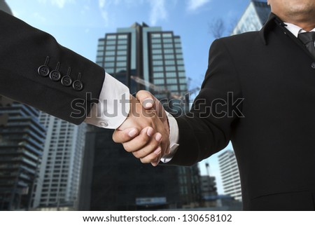 Business handshake on city background - stock photo