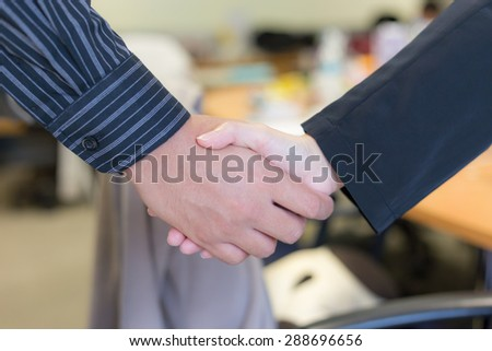 Business handshake on meeting room background