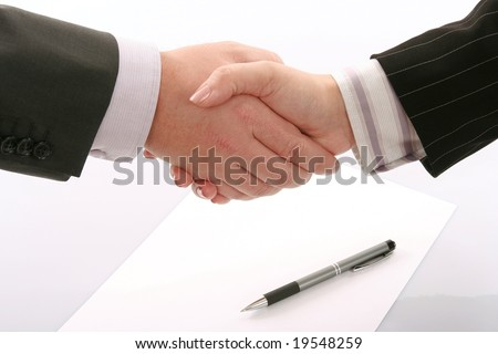 Business handshake over page with pen