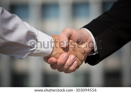 Business handshake, the deal is finalized between two enterprises. Man in black suit and woman in white one have signed the agreement. - stock photo