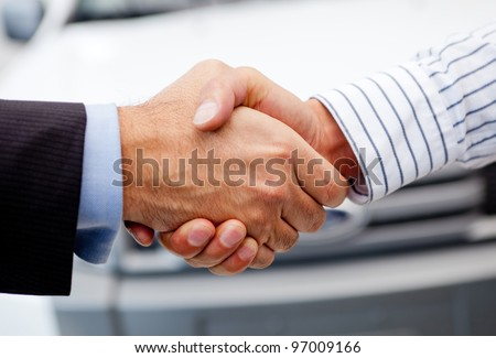 Business handshake to close the deal after buying a car - stock photo