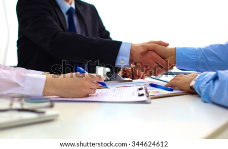 Business handshake. Two businessman shaking hands with each other in the office - stock photo