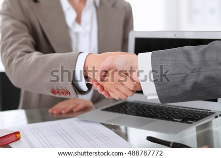 Business handshake. Two women are shaking hands after meeting or  negotiation.
