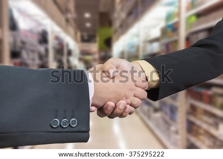 Business handshake with blur background of shopping mall - stock photo