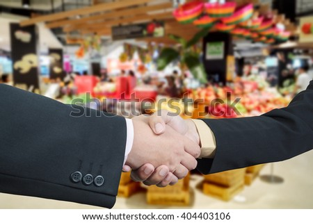 Business handshake with blur background of shopping mall market - stock photo
