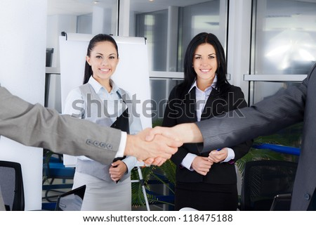 Business handshake with business people smile on background, colleagues shaking hands during meeting after signing agreement in office