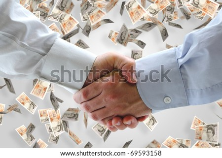 Business handshake with falling money in background - stock photo