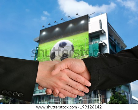 Business handshake with football display on building background - stock photo