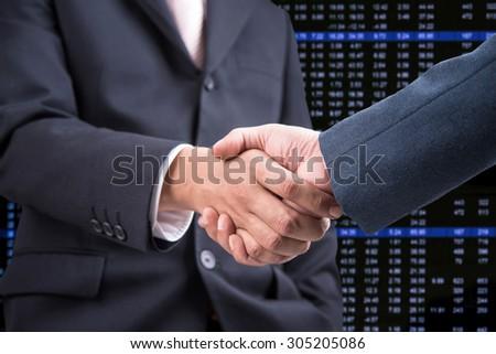 Business handshake with stock chart background  - stock photo