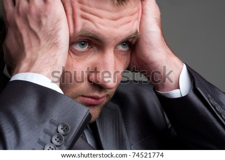 Business headache. Exhausted sad businessman holding his head - stock photo