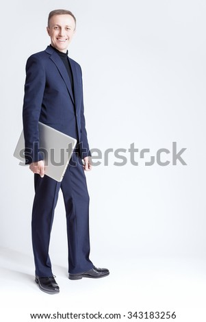 Business Ideas and Concepts. Portrait of Young Caucasian Handsome Business Man Holding Laptop Computer Against Gray Background.Vertical Image Orientation - stock photo