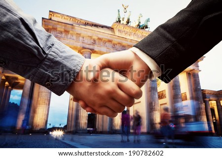Business in Berlin. Handshake on Brandenburg Gate background. Deal, success, contract, cooperation concepts  - stock photo