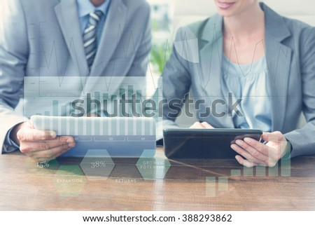 Business interface with graphs and data against business people discussing over tablet pcs - stock photo