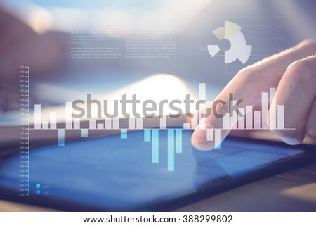 Business interface with graphs and data against businessman using laptop and tablet at desk - stock photo