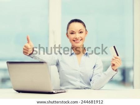 business, investing and technology concept - businesswoman with laptop and credit card in office showing thumbs up - stock photo