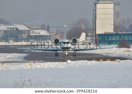 Business jet taxiing to the runway at the airport on a winter day