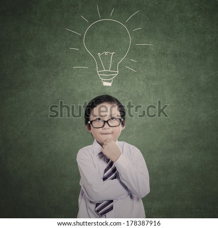 Business kid thinking pose with drawn lamp in class