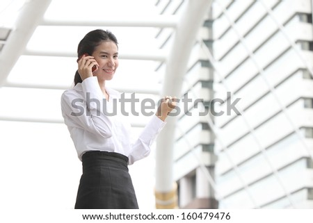 Business lady answering the phone with a smile, receiving good news  - stock photo