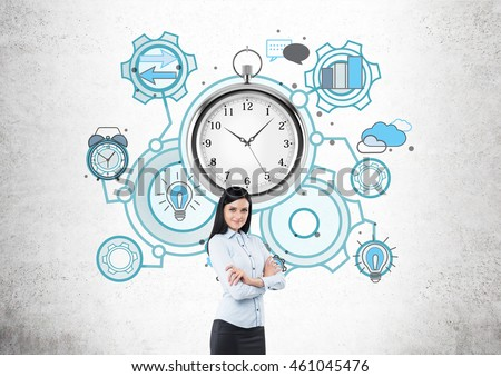 Business lady standing in front of concrete wall with giant stopwatch and multiple abstract sketches around it. She is smiling and has hands folded. Concept of time management and project deadline.
