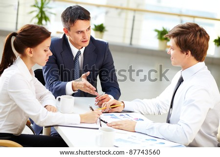 Business leader and his employees discussing the results of work - stock photo