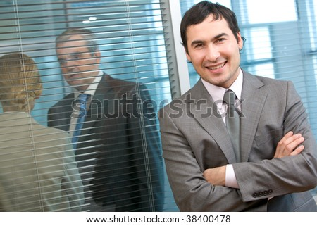 Business leader looking at camera with communicating people on background - stock photo