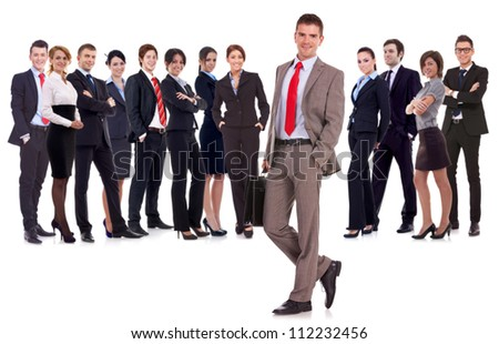 Business leader  with briefcase in his hand, isolated on white . young business man with suitcase looking at  the camera with a large business team behind him - stock photo
