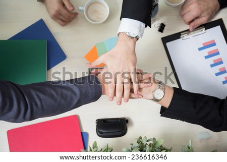 Business leaders joining hands above the table - stock photo