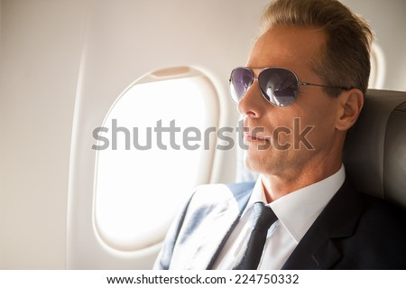 Business life. Confident mature businessman in sunglasses sitting at his seat in airplane  - stock photo