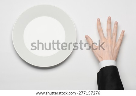 Business lunch and healthy food theme: man's hand in a black suit holding a white empty plate and shows finger gesture on an isolated white background in studio top view - stock photo