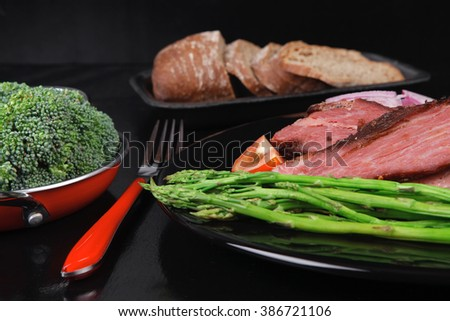 business lunch fresh roast beef meat slices on black plate cutlery asparagus boiled broccoli rye bun on wooden table