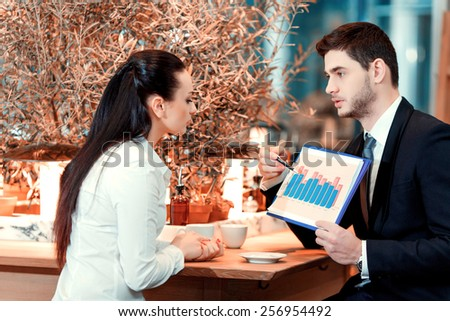Business lunch. Handsome young man in suit pointing at clipboard with analytics while sitting at the restaurant with his female colleague  - stock photo