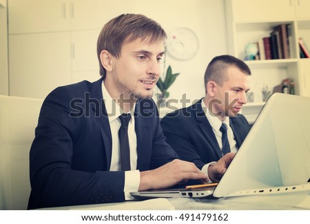 Business male assistant wearing formalwear using laptop and sitting with coworkers in company office