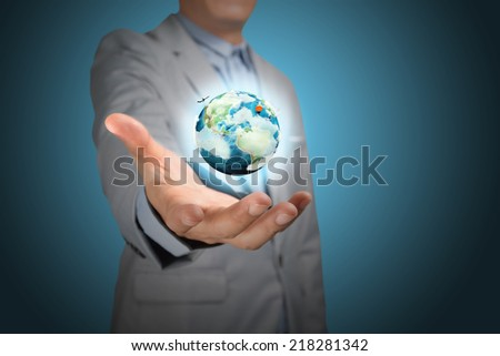 Business male hand hold earth globe on blue background. Elements in this image furnished by NASA.