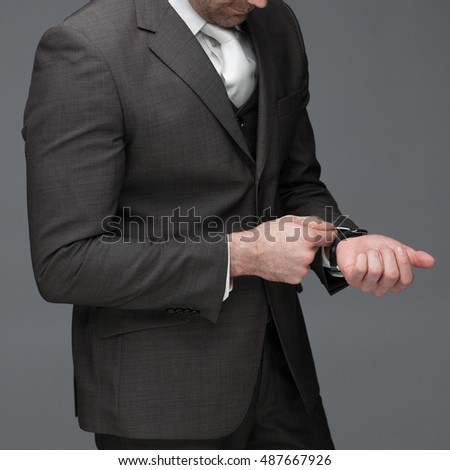 Business man adjusting his sleeve, on a grey background, stock picture