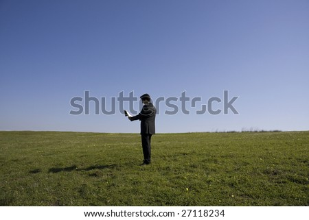 Business man alone on a field reading a newspaper