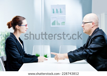 business man and business woman discussing facing each other in a polite discussion - stock photo