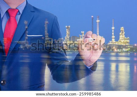 Business man and Oil refinery at twilight background - stock photo