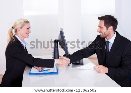 Business man and woman shaking hands over the top of a desk as they clinch a deal - stock photo