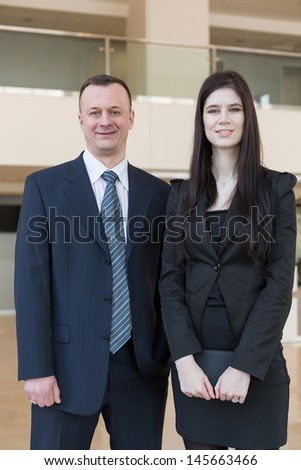 Business man and woman standing in the room