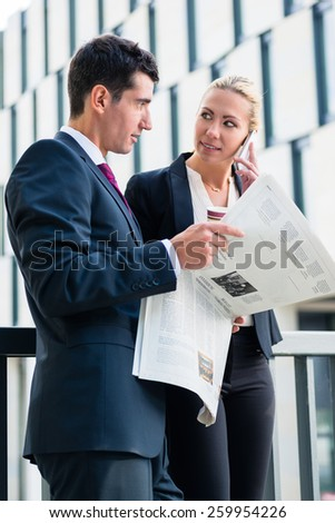Business man and woman with paper and phone in front of office building in the city - stock photo