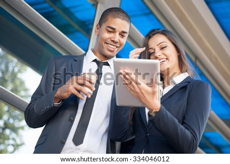 Business man and woman with tablet computer ,talking - stock photo