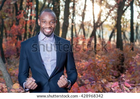 business man arms oustretched forest green concept
