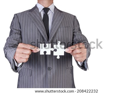 business man assembling jigsaw puzzle isolate on white background with clipping path - stock photo