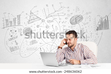 Business man at desk with hand drawn charts at the background