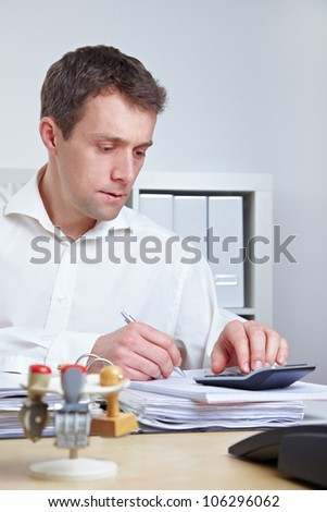 Business man at his desk using a calculator in the office - stock photo