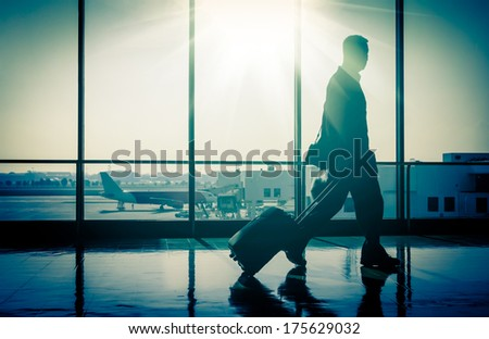 Business man at international airport moving to terminal gate for airplane travel trip - Mobility concept and aerospace industry flight connections - Sunshine on cold blue nostalgic filtered look - stock photo