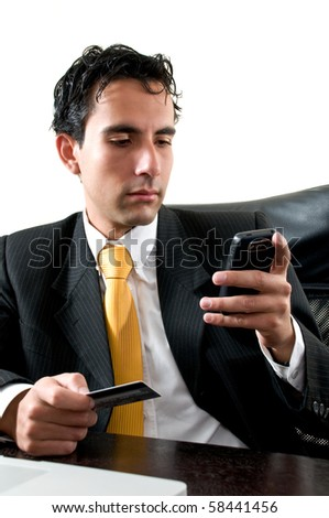 Business man at office paying with his credit card trough his cell phone - stock photo