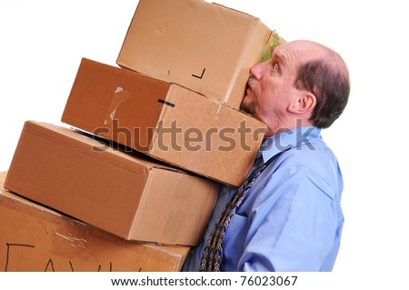 Business man carrying  heavy boxes while precariously balancing them in his arms. - stock photo