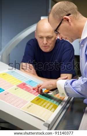 Business man checks a printed calendar with a swatch book - stock photo