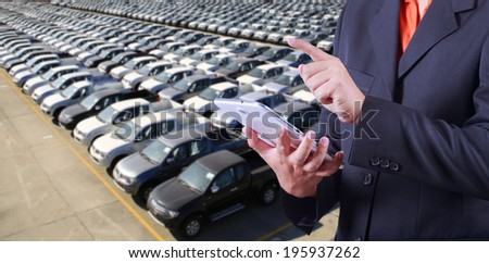 Business man counting motor vehicles in storage yard - stock photo